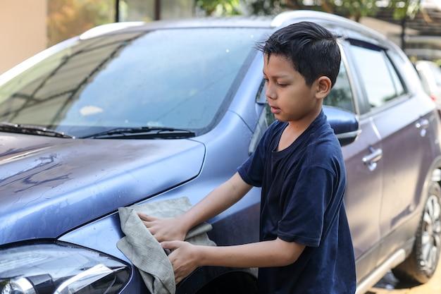 Азиатский мальчик вытирает кузов машины