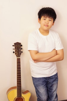 Asian boy with crossed arms standing near acoustic guitar.