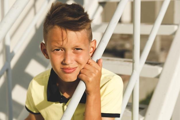 階段に髪のアジアの少年
