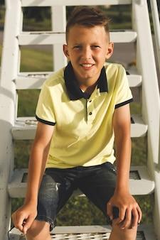 笑顔の髪型を持つアジアの少年。日光への階段で
