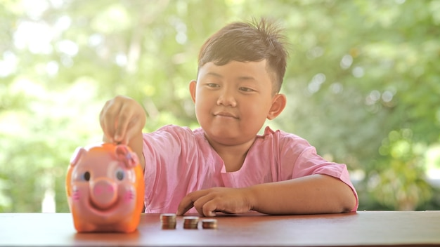 Asian boy with a happy smile fun putting coins in a piggy bank