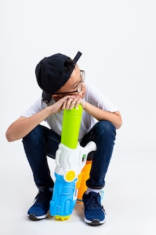 Asian boy with squirt gun on white background