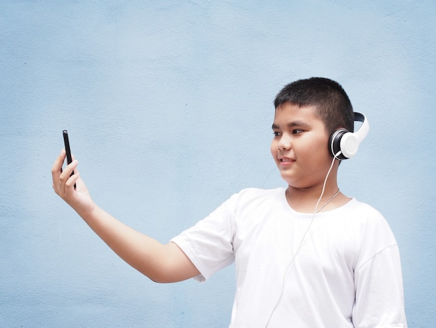 Asian boy with white shirt wearing headphone and playing mobile phone over blue wall background.