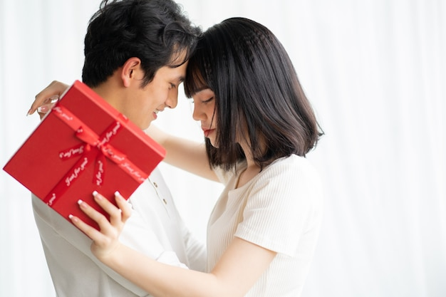 Asian boyfriend gives gifts to his girlfriend on valentine's day
