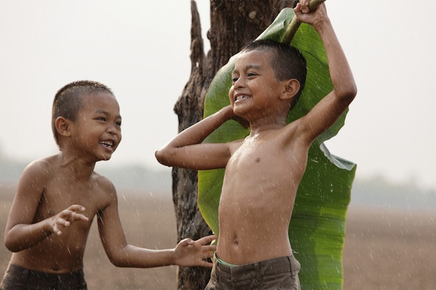 Asian boys are happy because they play in the rain. after a long drought