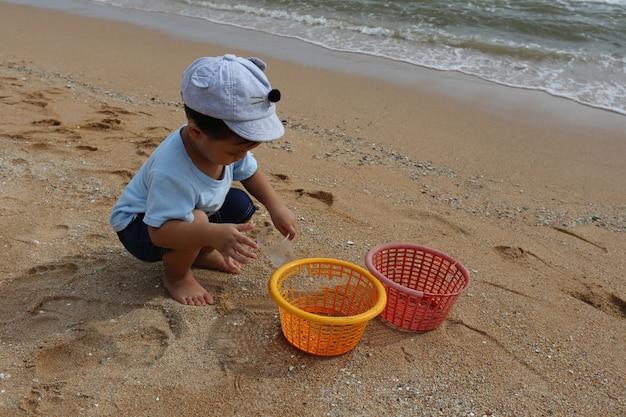 アジアの男の子は晴れた日にビーチの砂で遊んでいます