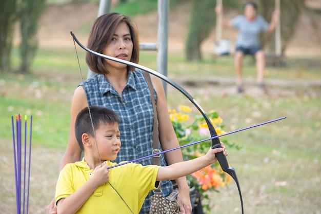 キャンプの冒険で弓を保持しているアジアの少年と背景のぼやけた木の後ろに立っている女性。