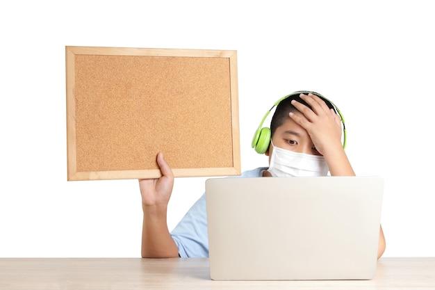 아시아 소년들은 집에서 화상 통화를 통해 온라인으로 학습하며 랩톱 컴퓨터를 사용하여 교사와 대화합니다.