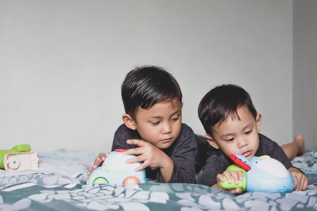 プレイルームでおもちゃの車を遊んで一緒に横たわっているアジアの男の子