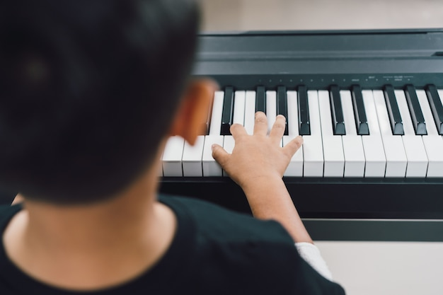 An asian boys  playing the piano.