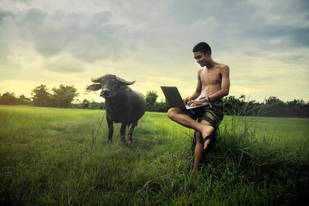 Азиатские мальчики, обучающиеся онлайн-обучением с ноутбуком на открытом воздухе, в сельской местности