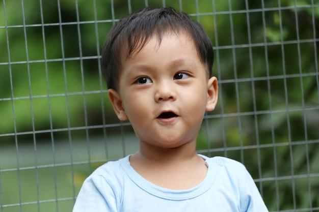아시아 소년들은 동물원에 있는 동물들을 큰 관심과 놀라움으로 바라보고 있었습니다.