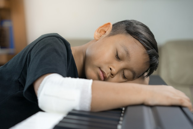 An asian boys at the wounded hands are  sleep on the piano.