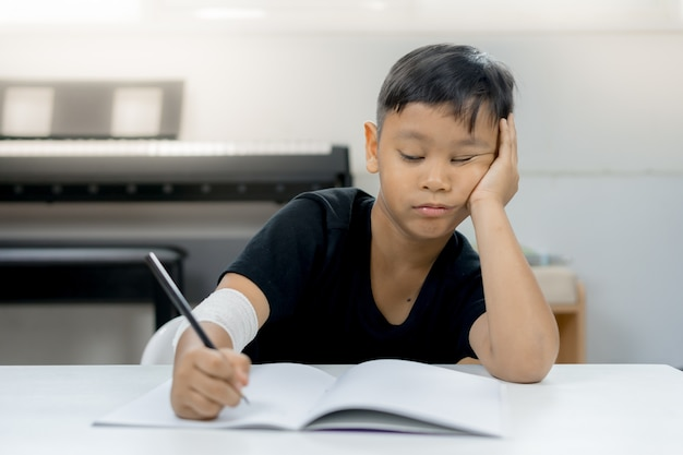 An asian boys at the wounded hands are weary of writing a notebook