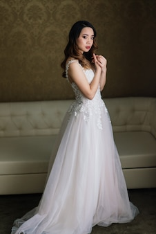Asian bride in wedding dress in hotel sitting on the bed, standing near window, morning
