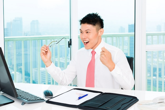 Asian broker trading at stock exchange in office