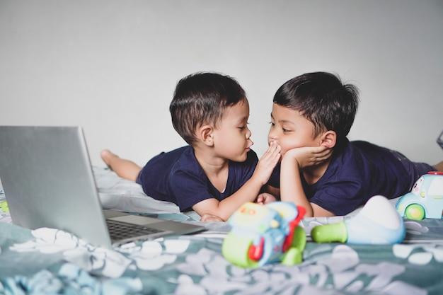 彼らのかわいいジェスチャーでラップトップやおもちゃと一緒に遊んでいるアジアの兄弟姉妹