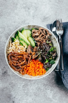 Asian buddha bowl on gray baclground. grilled beef,  sprouted mung bean, topinambour noodles