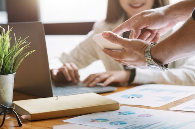 電算機で財務報告の状況を分析し、議論するアジアのビジネス顧問会議。