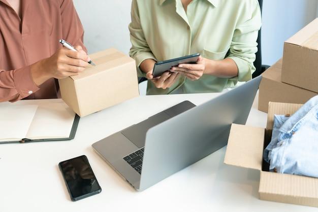 온라인 상점의 포장 상자와 함께 집에서 일하는 아시아 비즈니스 커플 소유자는 고객, 알파 세대 라이프 스타일 개념에 제품을 제공하기 위해 준비합니다.