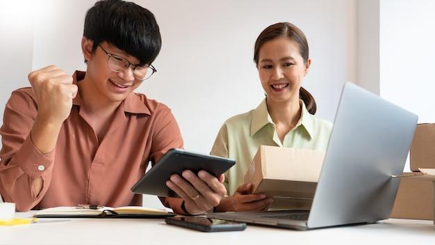 온라인 상점의 포장 상자로 집에서 일하는 아시아 비즈니스 커플 소유자가 고객에게 제품을 제공 할 준비를합니다.