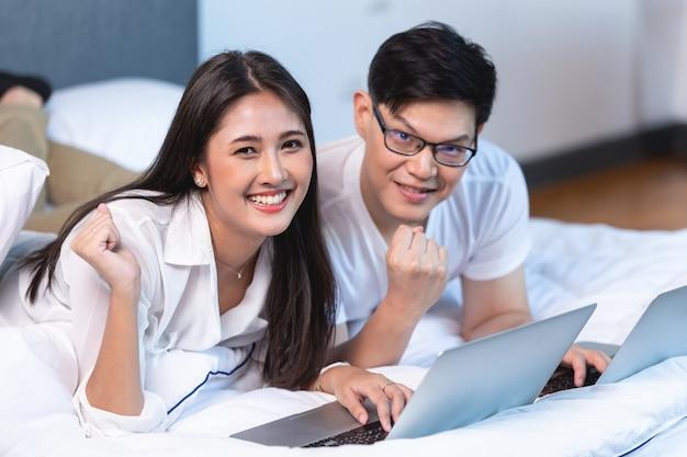 Азиатская бизнес-пара работает дома на кровати с ноутбуком счастливым, наслаждаясь с успехом портрет, глядя на камеру.