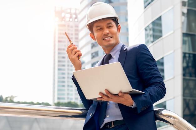 アジアのビジネスエンジニアマネージャー男立って、屋外の都市でラップトップで作業します。