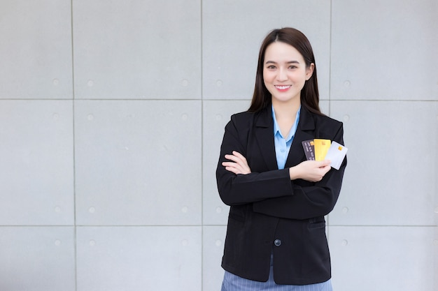 フォーマルな黒のスーツを着たアジアのビジネス女性が手にクレジットカードを持って見せます
