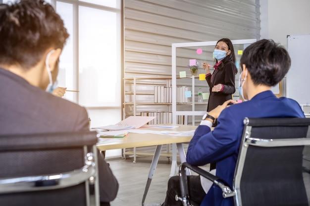 보호 마스크를 쓴 아시아 비즈니스 여성이 아이디어를 공유하기 위해 메모를 게시하는 것을 제공합니다. 브레인스토밍 개념입니다.