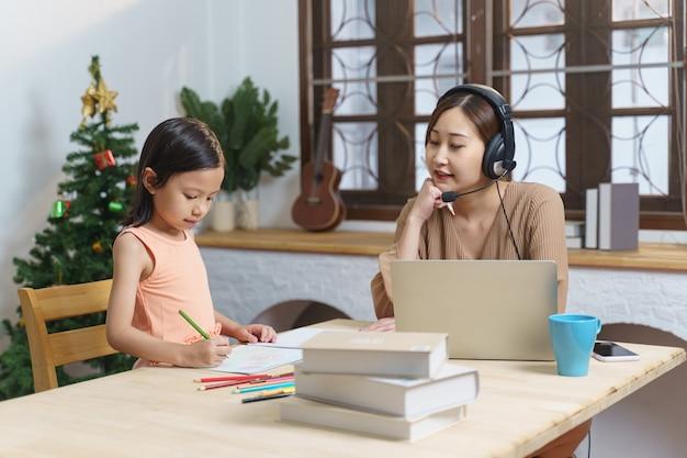 딸이 아파트에서 숙제를 하는 동안 노트북으로 일하는 아시아 여성