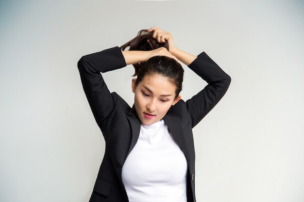 Asian business girl grab pony tail hair as ready to working on white wall