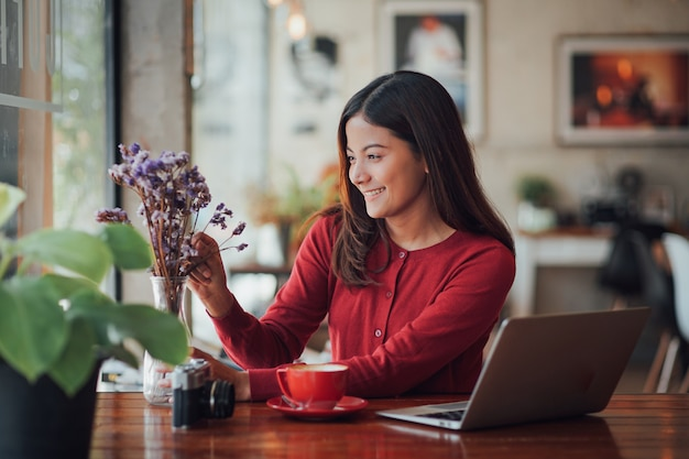 Asian business girl working and drinking coffee in cafe with laptop