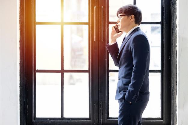 窓際に立つ眼鏡のアジアのビジネスは、電話をかけるためにスマートフォンを使用し、ビジネスマンはスマートフォンを使用して働いています。