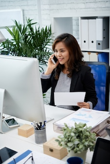 Asian business lady sitting in office, holding document and talking on mobile phone