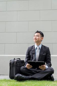 都市の公園でポータブルコンピューターを使用してアジアのビジネス男性。彼は探しています