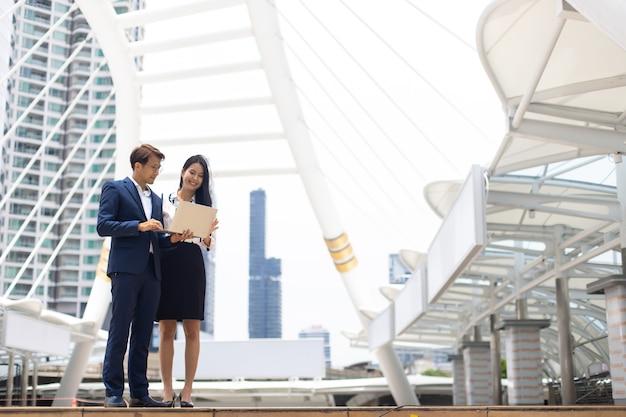 オフィスビルの外に立っているラップトップコンピューターに取り組んでいるアジアのビジネスの男性と女性。