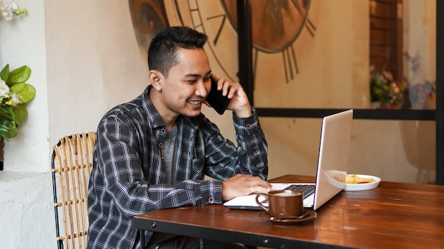 Азиатский деловой человек звонит с работой в кафе