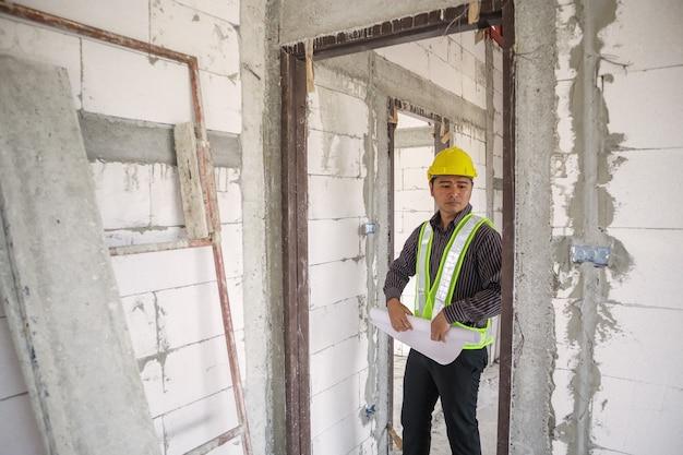 Азиатский деловой человек инженер-строитель в защитном шлеме и чертежах бумаги под рукой на строительной площадке