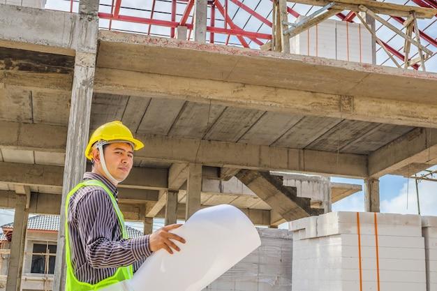 주택 건설 현장에서 보호용 헬멧과 청사진 종이를 입은 아시아 사업가 건설 엔지니어