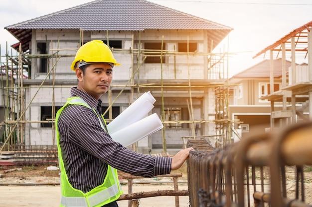 住宅建設現場で棒鋼を見ている手に保護ヘルメットと青写真の紙のアジアのビジネスマン建設エンジニア労働者