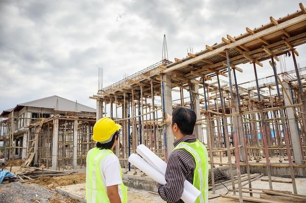 보호 헬멧에 아시아 비즈니스 남자 건설 관리자 및 엔지니어 작업자 집 건물 사이트에서 손에 청사진 종이를 개최