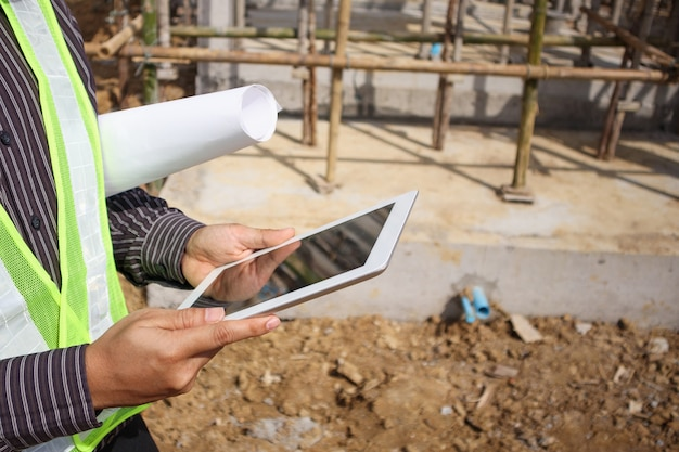 保護用のヘルメットでアジアビジネス男建設マネージャーとエンジニアワーカーが建設現場でタブレットコンピューターを使用して手に青写真紙を保持します。