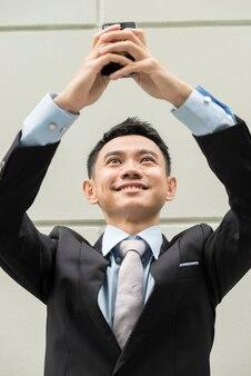 電話で自画像をやっているアジアのビジネスマン。彼は笑っている