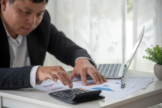 Asian business man hands using calculator counting tax financial bill tax audit finacial concept