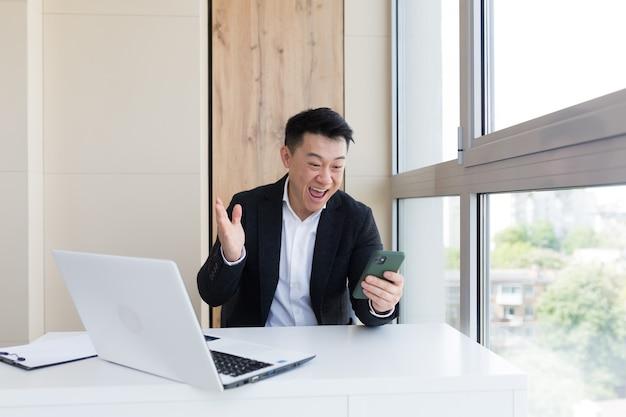 感情の勝者または勝利と携帯電話を見てオフィスでアジアのビジネスマン