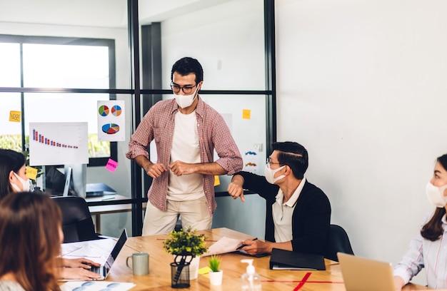 コロナウイルスの検疫中のアジアのビジネスマンは、プロのビジネス会議のグループとオフィスで戦略を議論し、新しい通常の肘で揺れる保護マスクを身に着けています