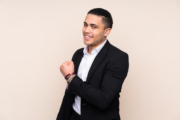 승리를 축 하하는 베이지 색 벽에 고립 된 아시아 비즈니스 남자