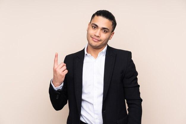 검지 손가락으로 가리키는 베이지 색 벽에 고립 된 아시아 비즈니스 남자 좋은 생각