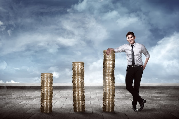 Asian business man leaning on the pile of coins