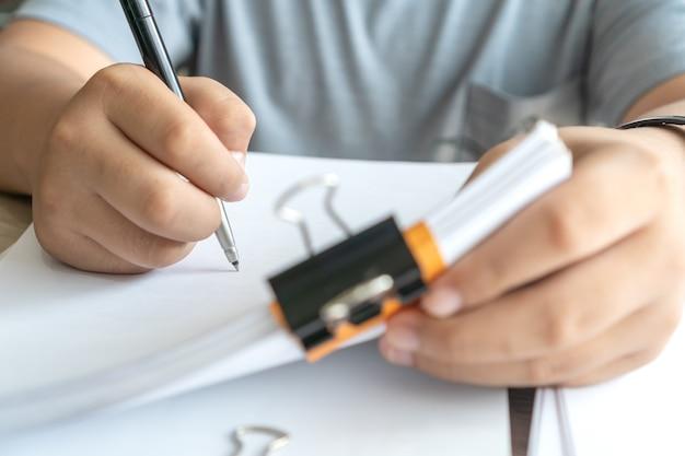 Менеджер по азиатскому бизнесу проверяет и подписывает заявителя, заполняя документы, отчеты, документы, форму заявки компании или регистрируя претензию в офисе. документ отчета и концепция бизнеса занята